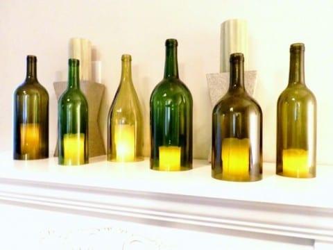 interessante Wanddekoration mit Kerzen in grünen Weinflaschen