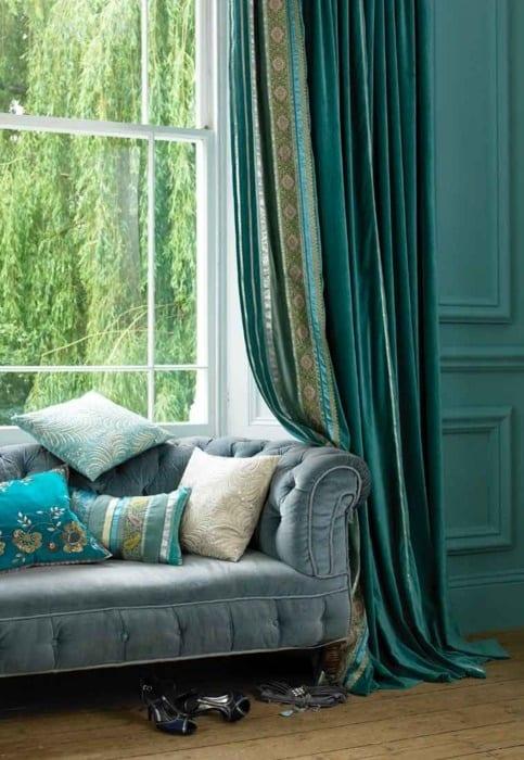 Sofa in grauem Plüsch mit türkisen Kissen und Gardinen