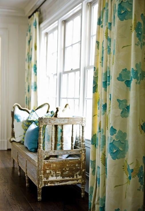 rustikale Wohnraumeinrichtung mit Holzbank und Vorhang in gelb und türkis