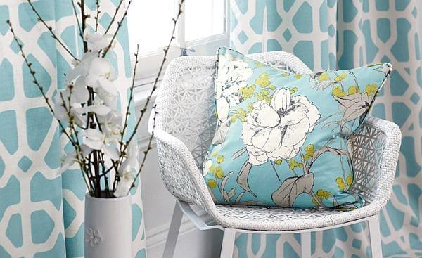 Wohndekoration mit weißem Stuhl und türkiser Kissen mit blumen