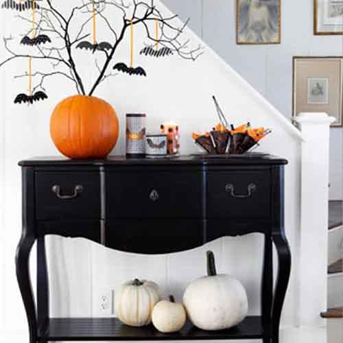 schlichte Halloween Deko mit weißen Kürbissen ünter schwarzer Kommode