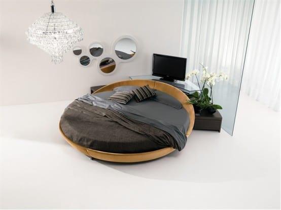 Schlafzimmer mit Rundbett aus Leder mit grauer Bettw'sche
