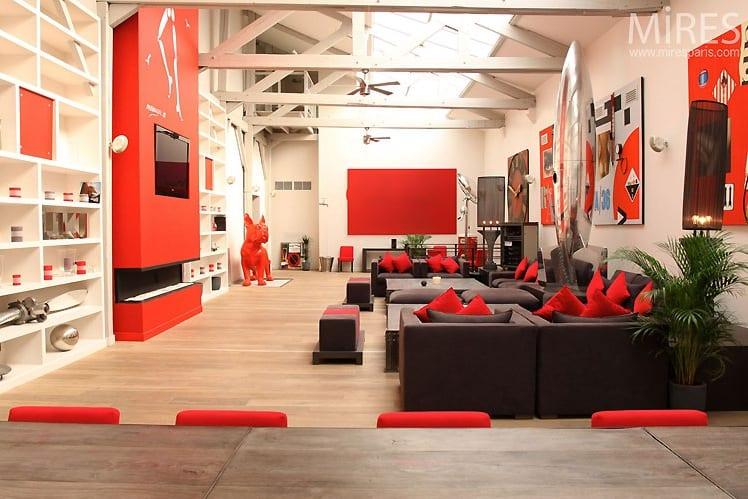 moderner Loft Wohnung mit schwarzem Sofa und roter Wandgestaltung