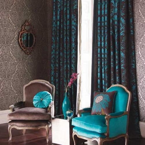 braune Vorhänge mit türkisem Blumenmuster und Sessel aus türkisem Plüsch