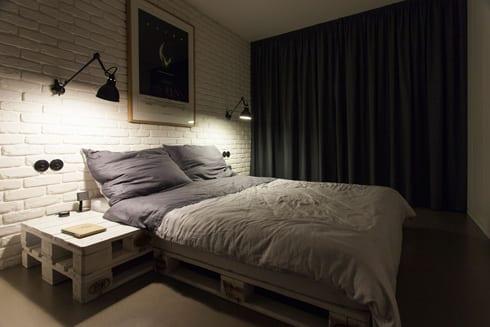 schlafzimmer-einrichtung-mit-ziegelwand-und-palettenbett-mit-palettennachttisch-und-in-weiß