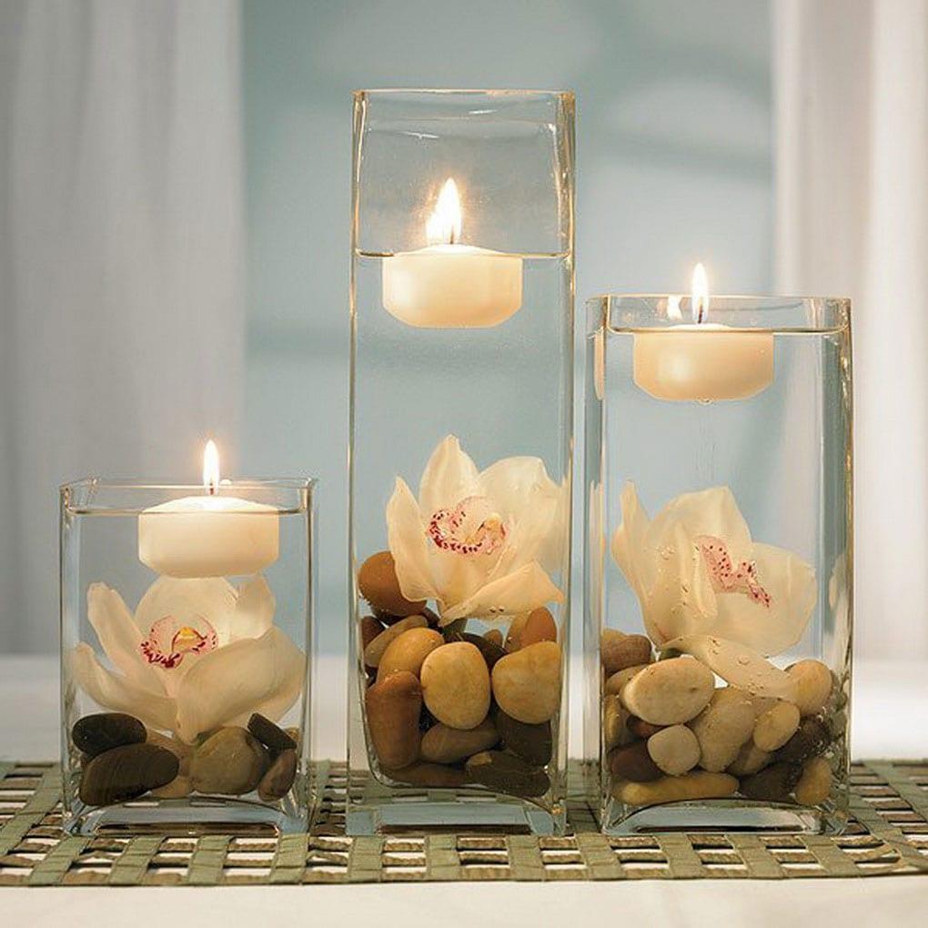 Kerzendeko in Glas mit Steinen und Blumen unter Wasser