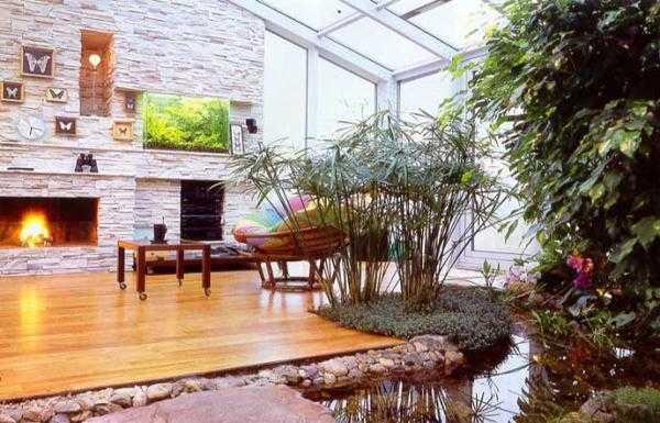 Wohnraum mit Holzboden und Wassergarten