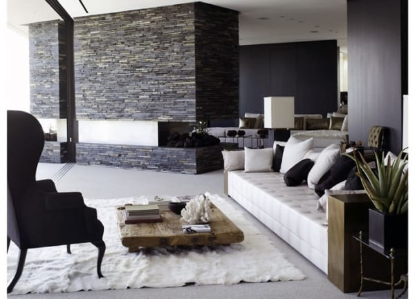 Wohnbereich mit Kamin aus Naturstein in der Mitte