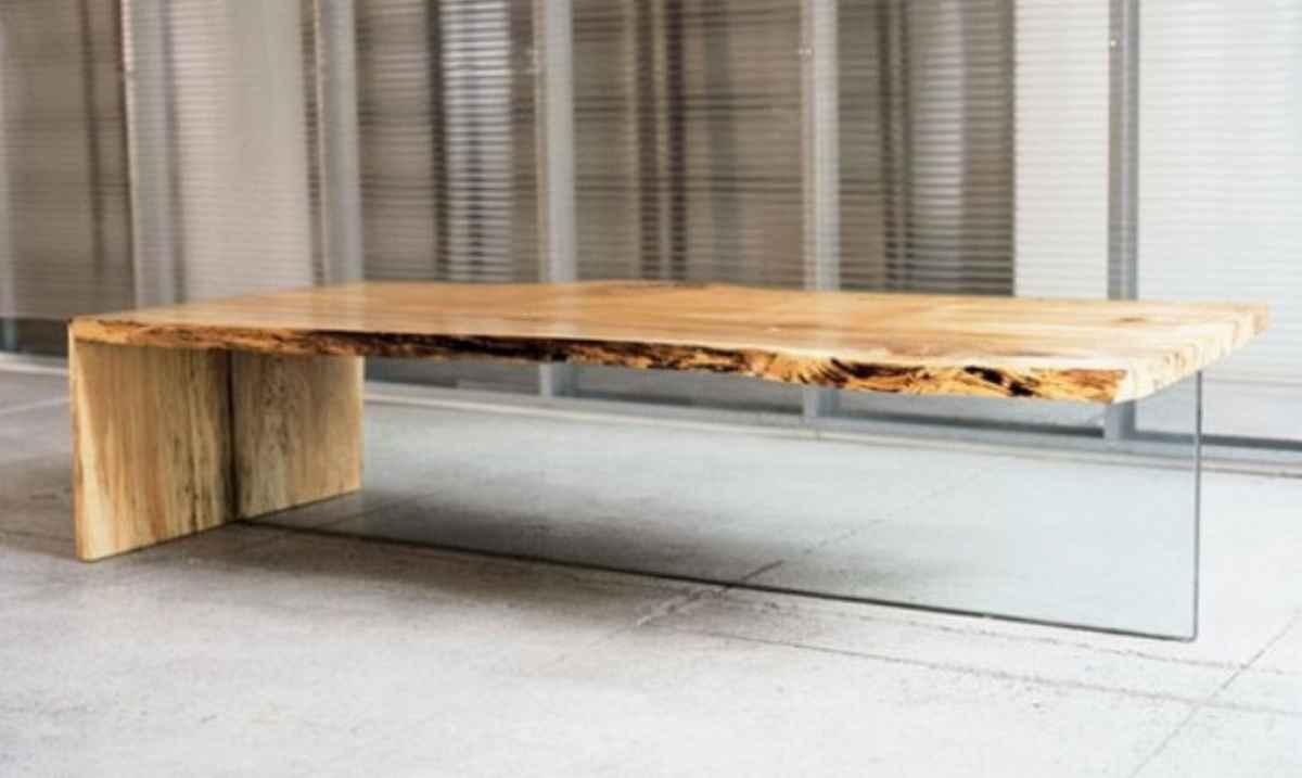 rustikaler couchtisch aus holzplatte und vertikal rechteckiger glasplatte auf natursteinboden