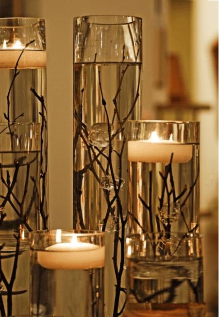 Tischdekoration mit Kerzen und Zweigen im Wasser