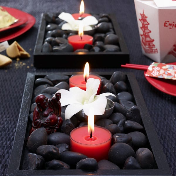 Tischdekoration in schwarz mit roten Kerzen in Schale mit Steinen