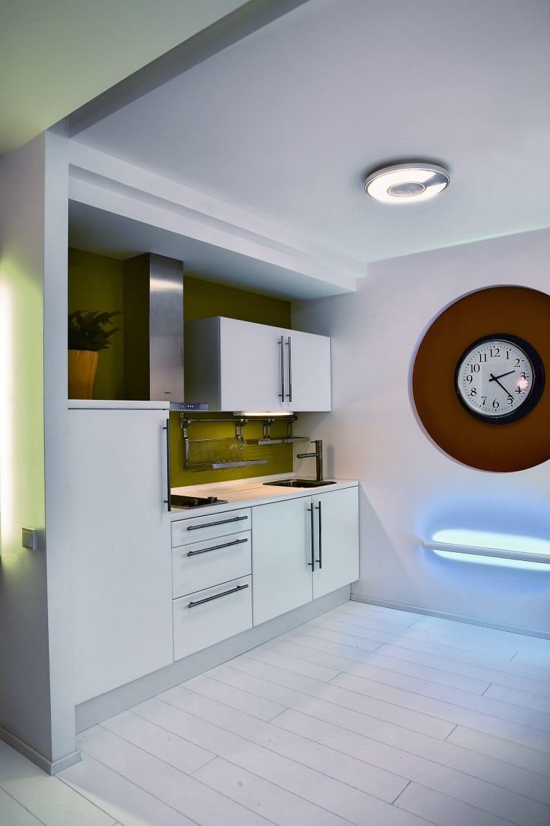 kleine Küche in weiß mit akzentierender grüner Wand und runden Formen