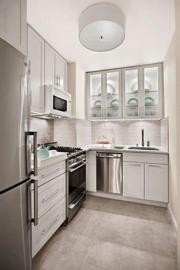 kleine-küche-in-weiß-kombiniert-mit-ziegelsteine-und-verglsten-küchenschränken