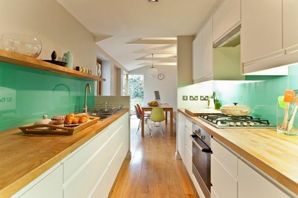 moderne-küche-in-weiß-mit-hölzerner-küchentheke-und-wandverkleidung-aus-glas