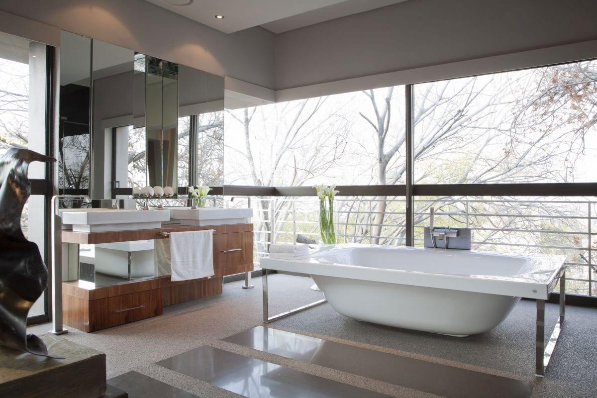 moderne Badeinrichtung mit Fensterwand und Badewanne mit Edelstahlrahmen