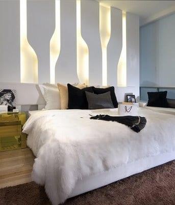 Schlafzimmer mit weißer Bettdecke und 3D Wandpaneelen