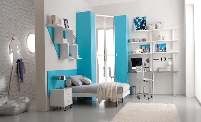 minimalistische Einrichtung des Kinderzimmers in weiß mit Rollbett und Eckschrank in blau