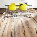 rustikaler Holzbodenbelag mit Glastisch und gelben Stühlen