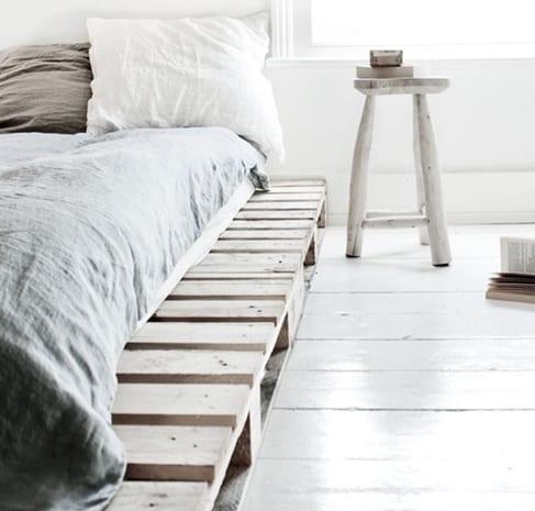 palettenbett-mit-hölzernem-stuhl-als-nachttisch