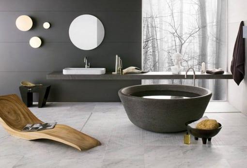 moderne Badeinrichtung mit Marmorboden, Holzliege und freistehender Badewanne aus Naturstein
