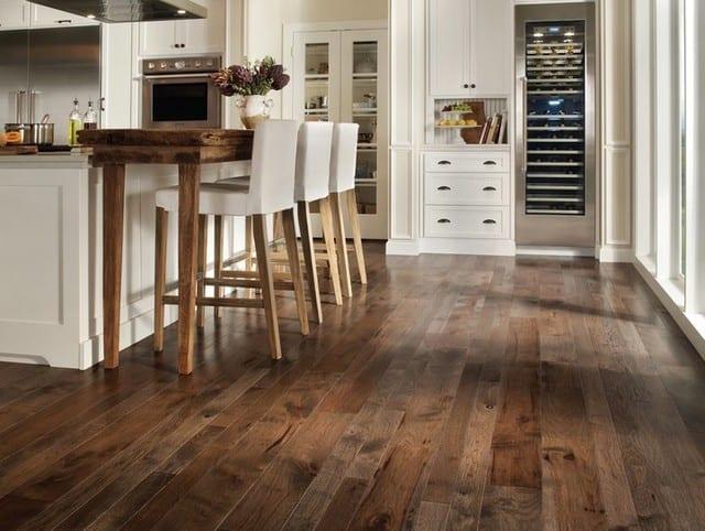 Kücheeinrichtung mit Holztheke und weißen Barhockern