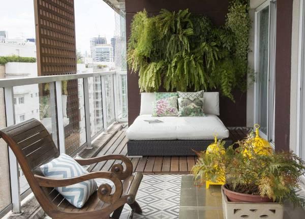 moderne Balkon-Einrichtung mit Holzboden und Rattanliege und Blumendeko an der Wand