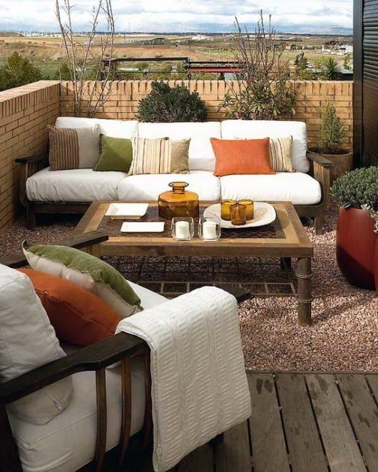 interessante Balkoneinrichtung mit Holzmöbeln auf Kiesboden