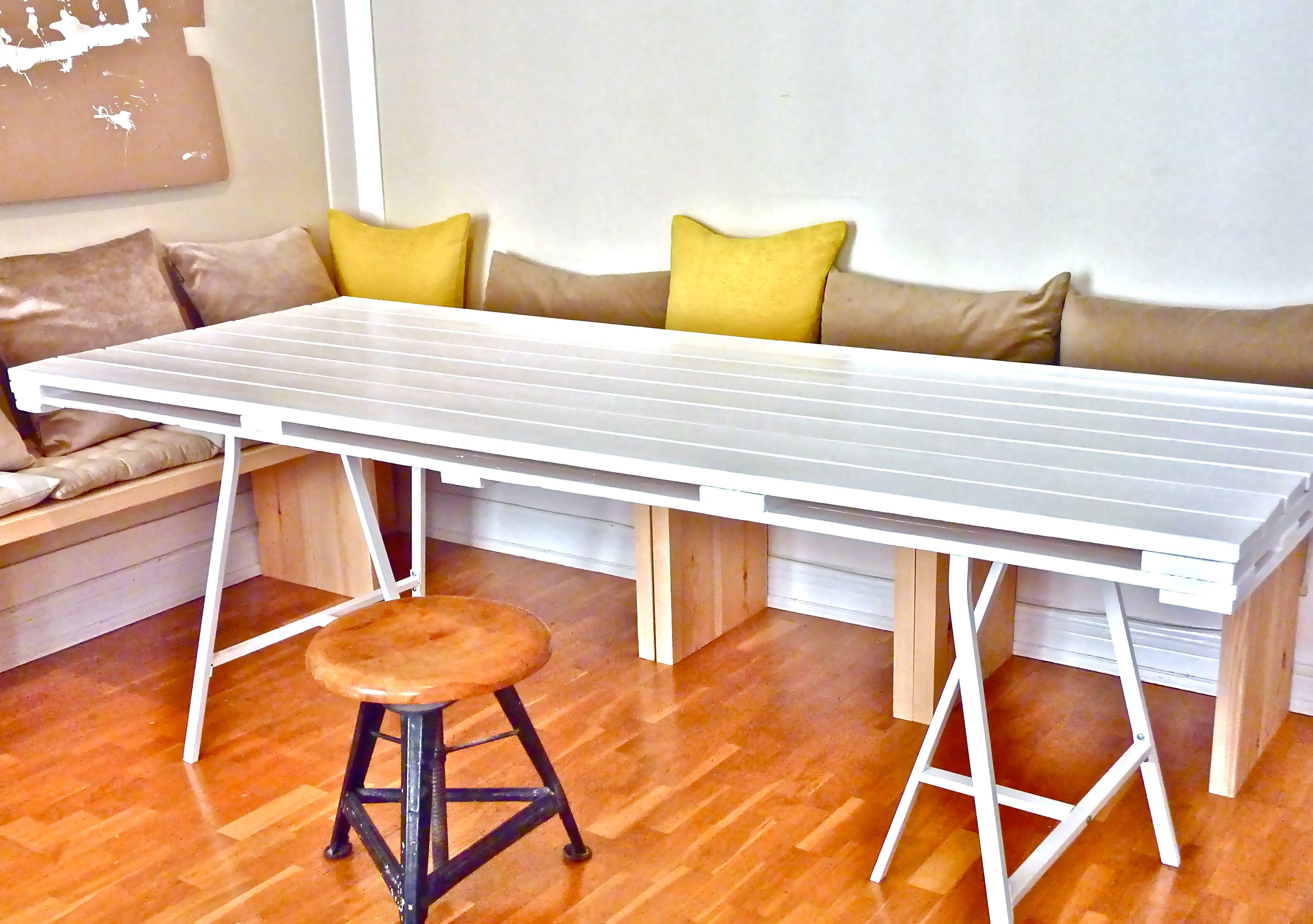 selbstgebauter Esstisch aus Paletten in weiß mit holzsitzecke und Kissen für die Küche
