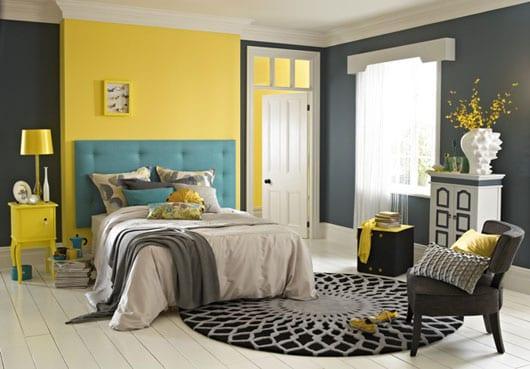 kreative schlafzimmergestaltung in grau und gelb mit weißem Holzboden und rundem Teppich