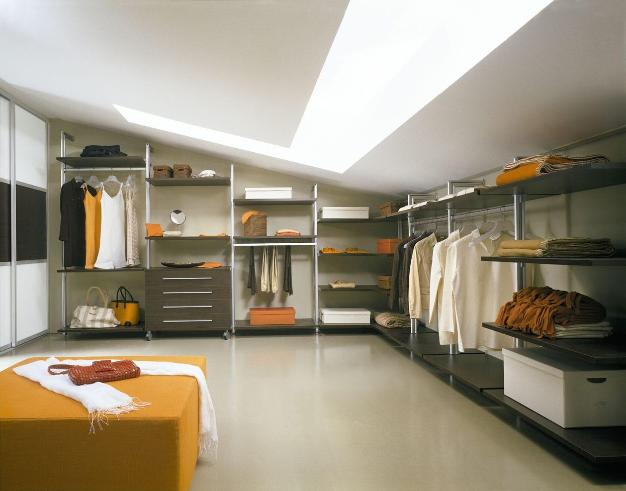 ankleidezimmer im dachraum mit interessantem oberlicht und offene Kleiderständern und rechteckigem hocker in gelb