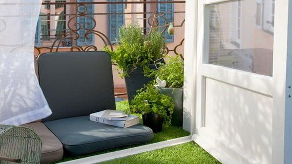 kreative Einrichtung kleiner Balkons mit Polsterkissen und Kunstgras