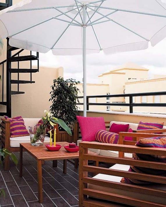 Einrichtungsidee für kleinen Balkon in Pink mit Holzmöbeln und Sonnenschirm