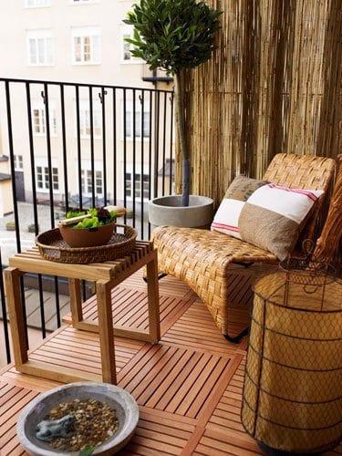Einrichtungsidee für kleinen Balkon mit Holzmöbeln und Schilfrohrmatte