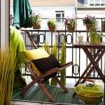Einrichtung kleiner Balkons mit Sessel und Grill in grün