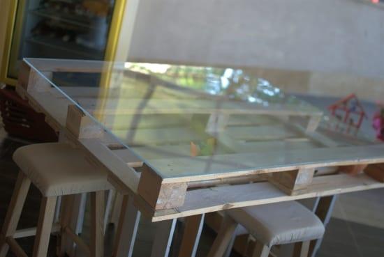 selbstgemachter quadratischer Bartisch aus europaletten mit Glasplatte und holzbarhockern