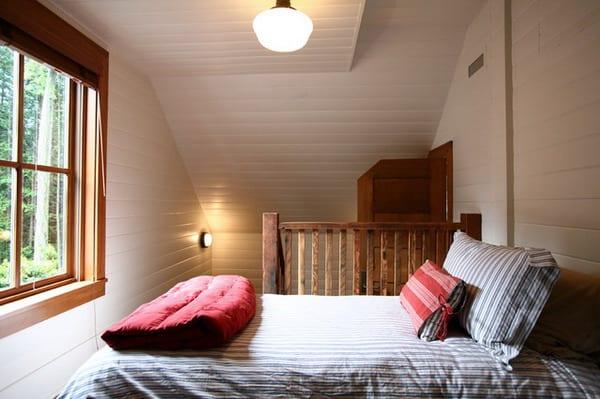 kleines schlaffzimmer in weiß am dach mit holzfenster und holzgelender