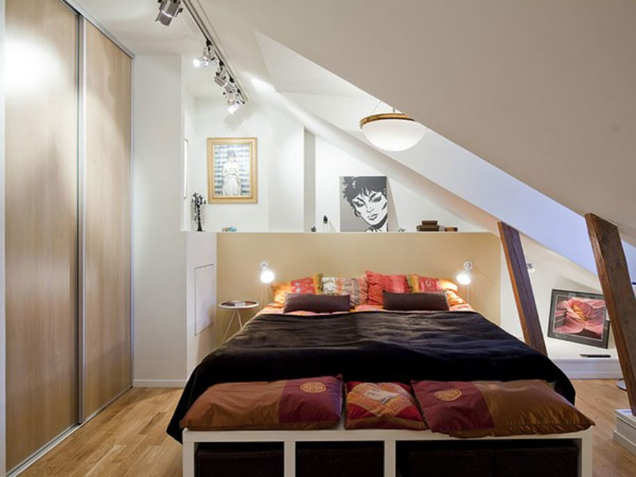 kleines schlafzimmer am dach mit eingebautem Kleiderschrank und doppelbett unter oberlicht