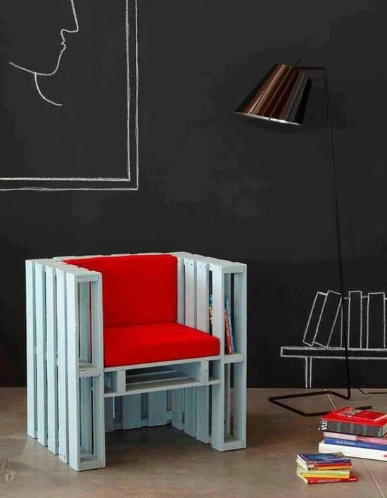 eleganter Sessel aus europaletten in weiß mit roten Sitzkissen und designer Stehleuchte vor schwarzer Wand
