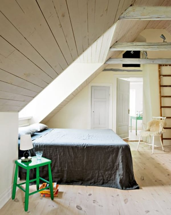 kleines schlafzimmer am dach mit doppelbett und holzeinrichtung