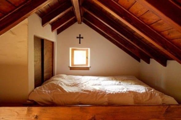 schlafzimmer im dachraum mit sichtbaren holzsparren