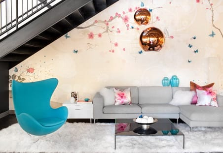 wohngestaltung mit sofa in grau und designerstuhl in blau unter metalltreppe
