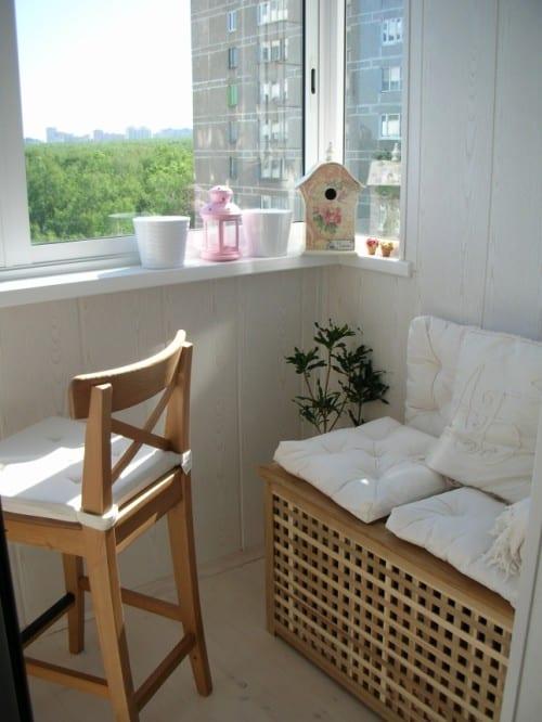 einfache und gemütliche Balkoneinrichtung in weiß mit Barhocker und Sitzfläche