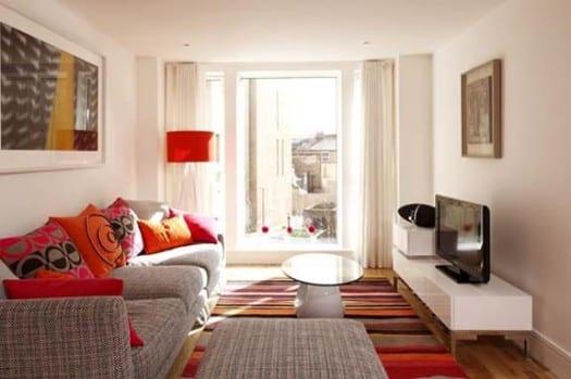 farbeinrichtung für kleine räume- bunter teppich-sofakissen in orange und pink-moderner weißer TV-schrank