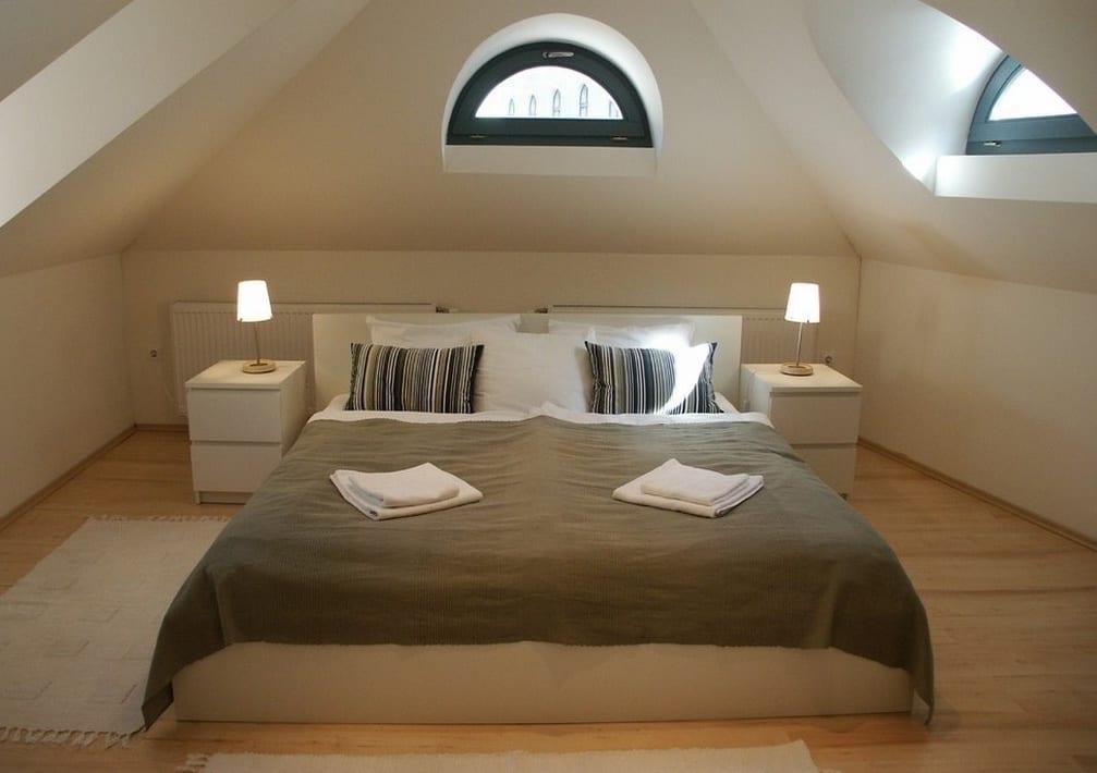Dachraum einrichtungs ideen mit doppelbet, holzboden und halbrunden Gauben