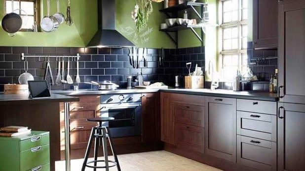 moderne Küche aus dunkelem Holz mit schwarzen Wandfließen und grüner Wand