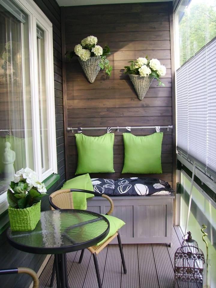 Balkon Einrichtungsidee mit Holz und hängenden Kissen als Rückenlehne in grün