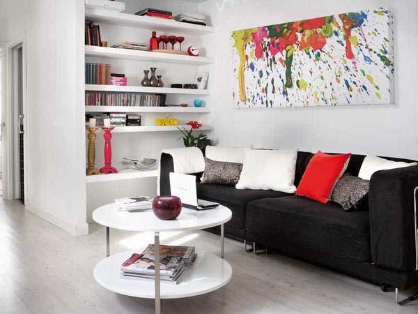 kleines wohnzimmer mit schwarzem sofa und weißem Rundtisch-weiße bücherregale in der nische-bunte wandgestaltung