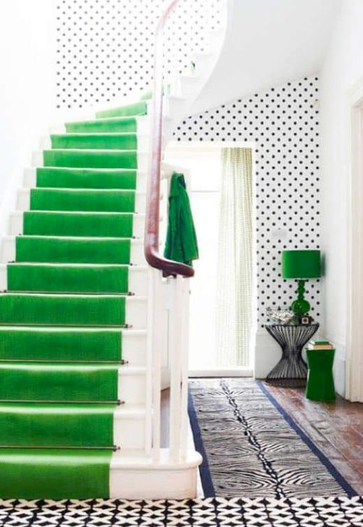 weiße Treppe mit grünem teppich und weiße wand mit schwarzen punkten