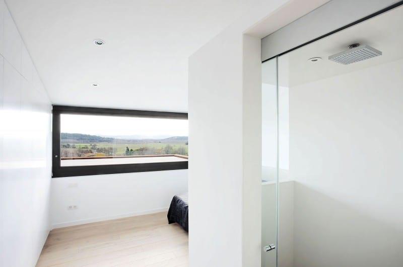 moderne Schlafzimmereinrichtung mit Dusche und längförmigem Fenster