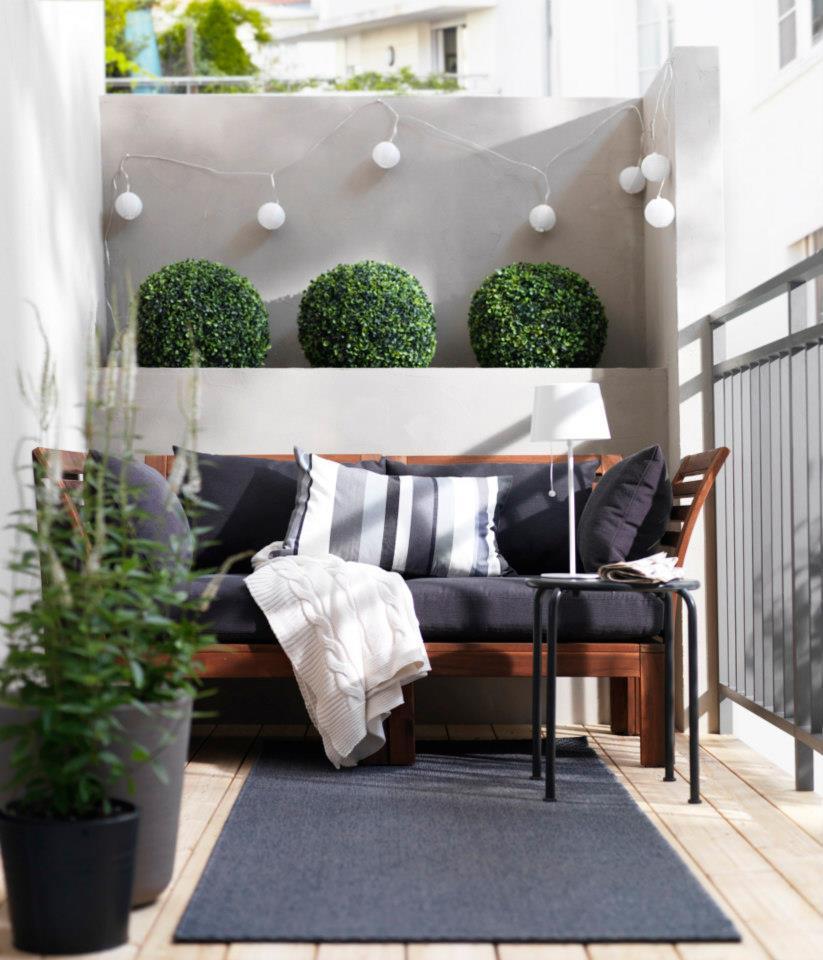 elegante Balkoneinrichtung in weiß und blau mit klenem Holzsofa und wandleuchten-deko
